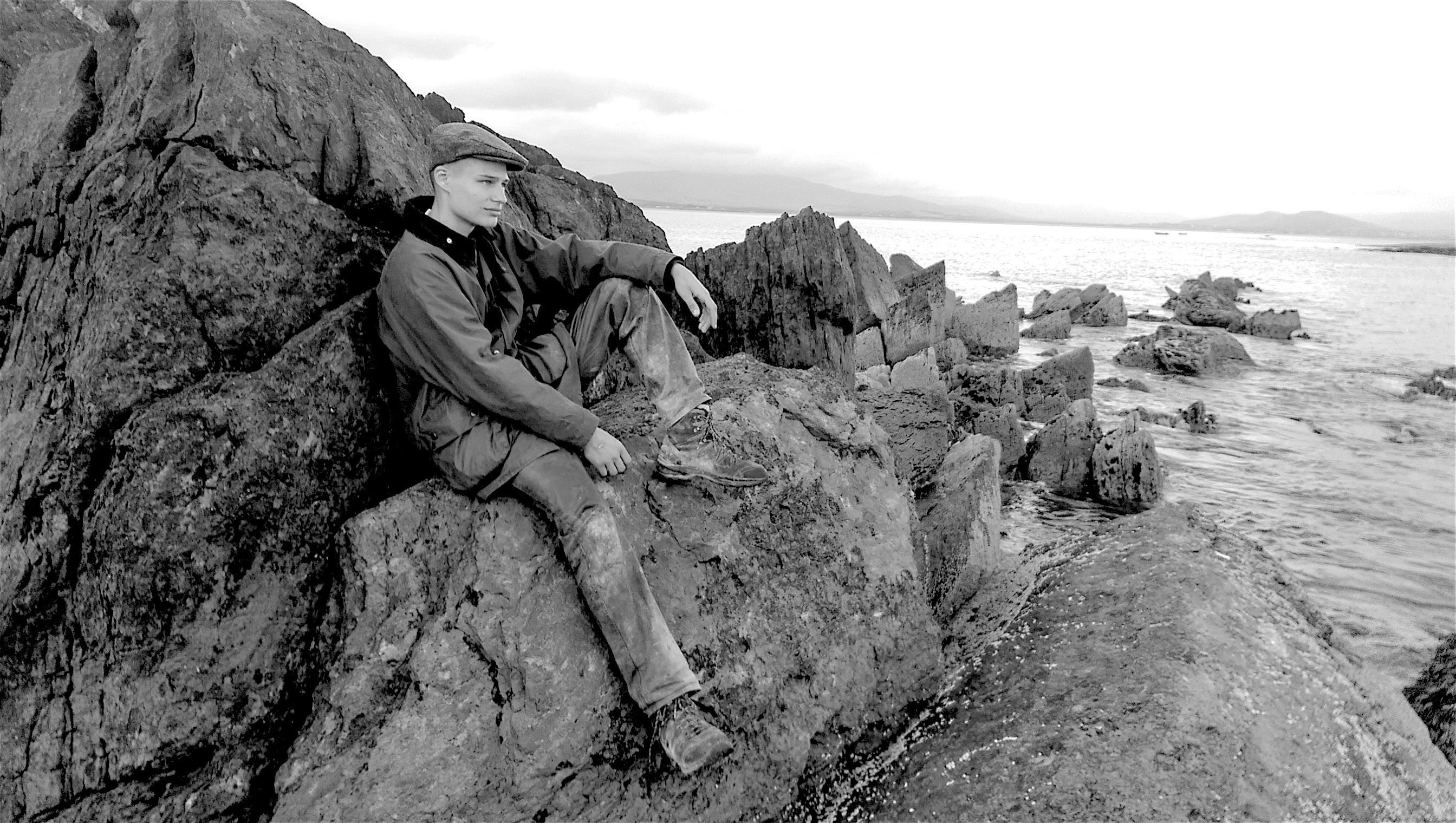 Junger Mann auf Felsen